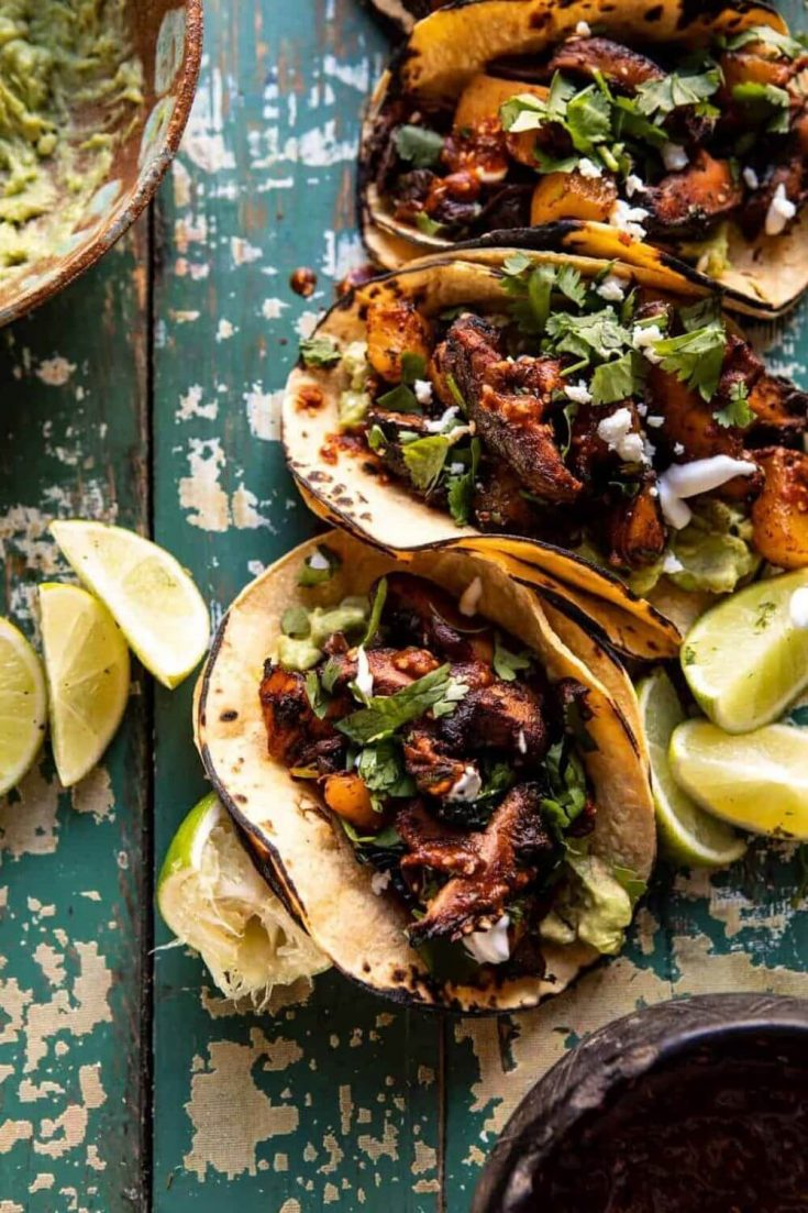 A line of loaded mushroom al pastor tacos topped with garlic lime special sauce.