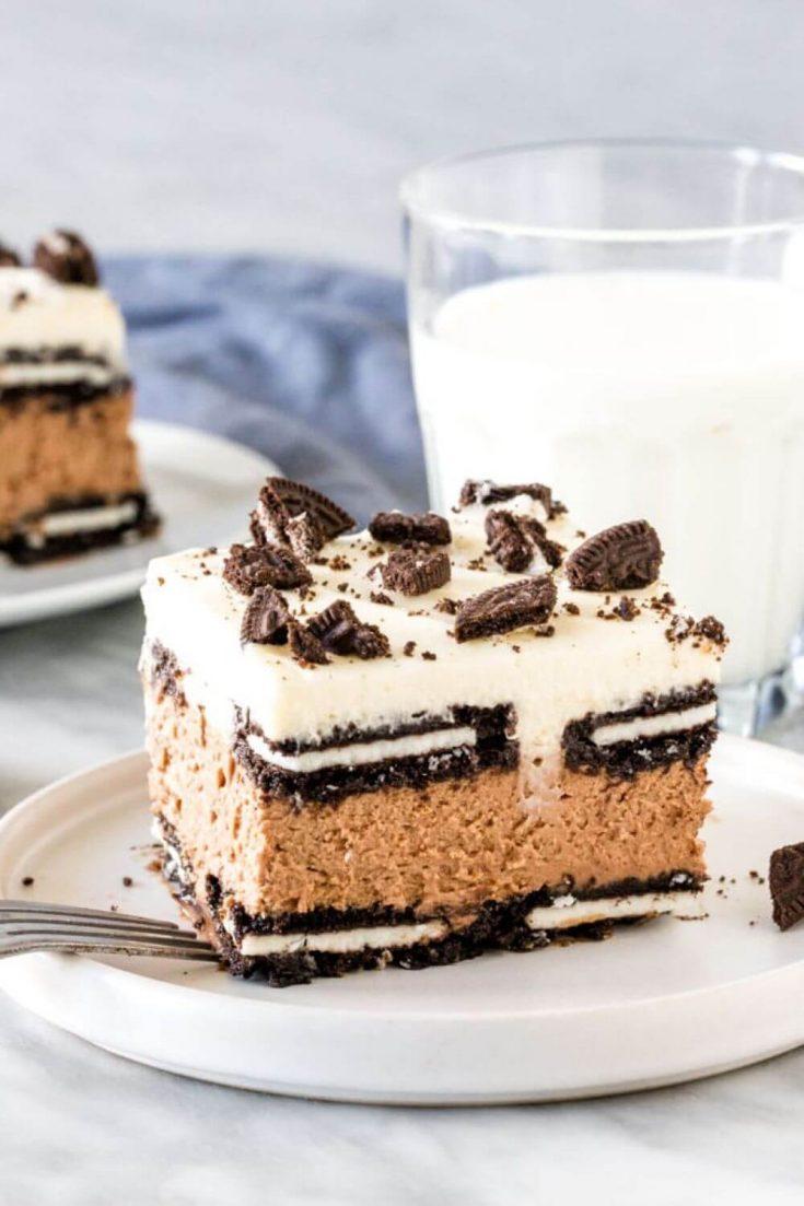A piece of oreo icebox cake near a glass of milk.