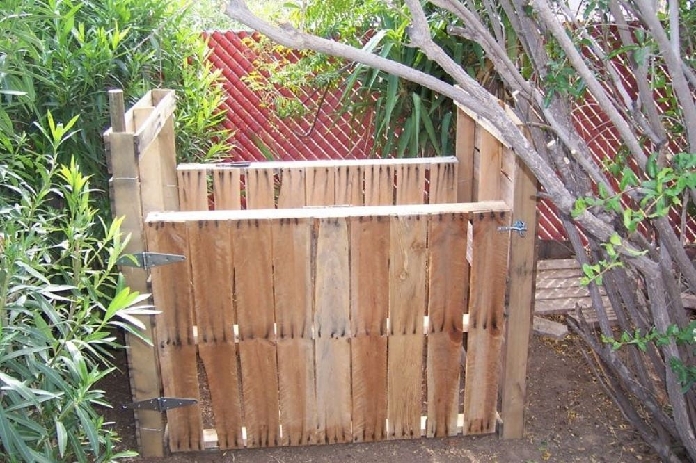 A pallet compost bin nestled in a variety of plants in someone's yard.