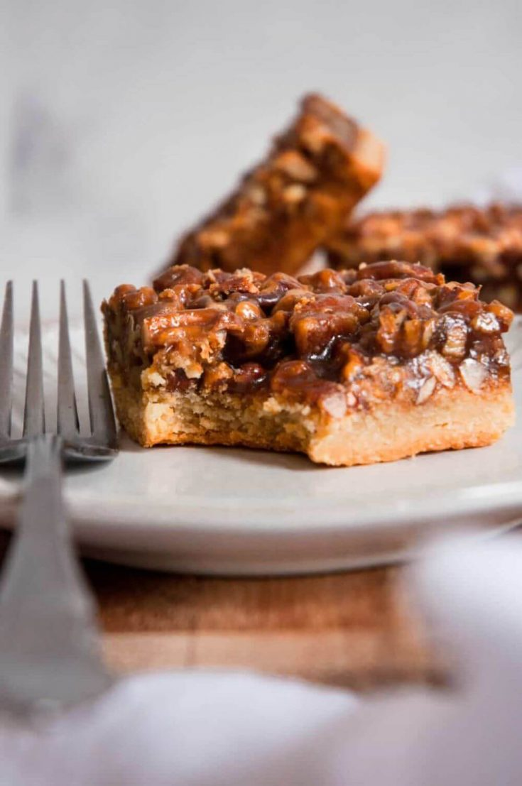 A healthy pecan pie bar with a bite taken out of the corner.