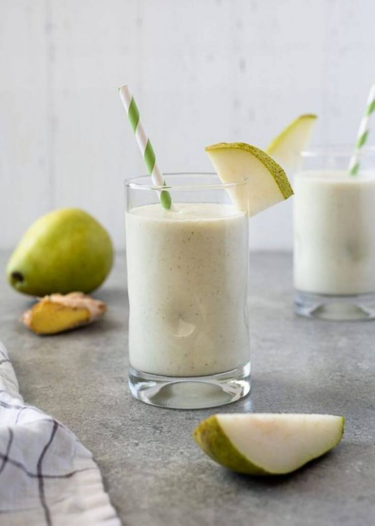 A delicious glass of pear ginger smoothie with a straw in it.