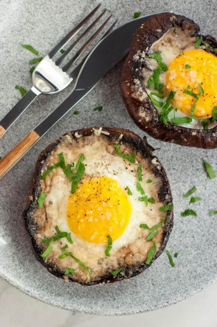 A plate of two portobello baked eggs topped with herbs.