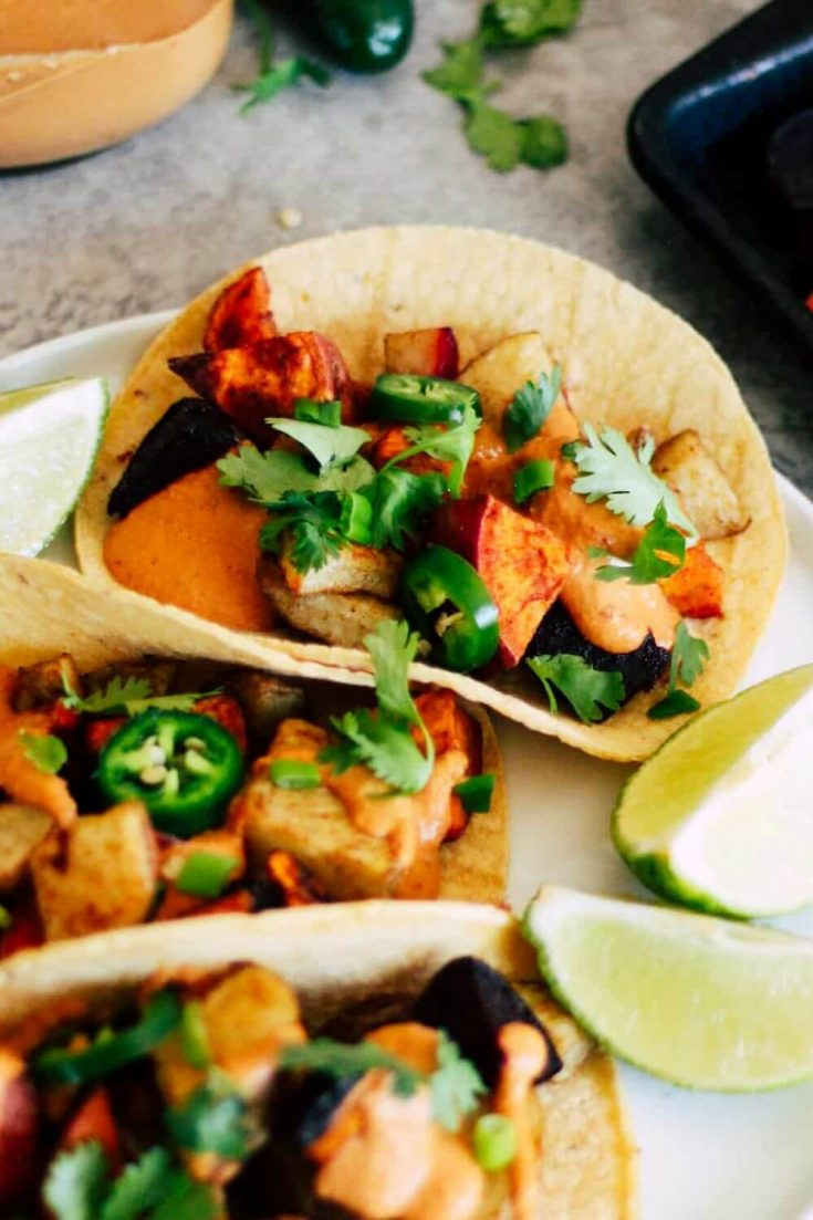 Three colorful roasted root vegetable tacos topped with sunflower seed queso.