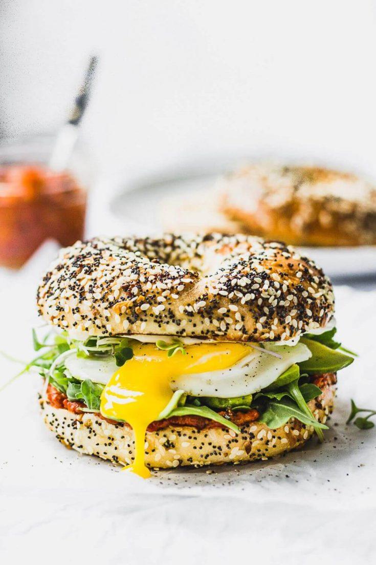 A delicious vegetarian romesco breakfast sandwich on a bagel.