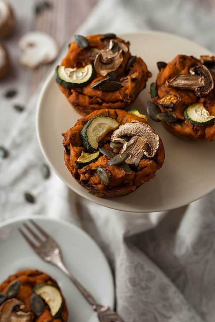 Several savory sweet potato muffins on a plate topped with mushrooms and zucchini.