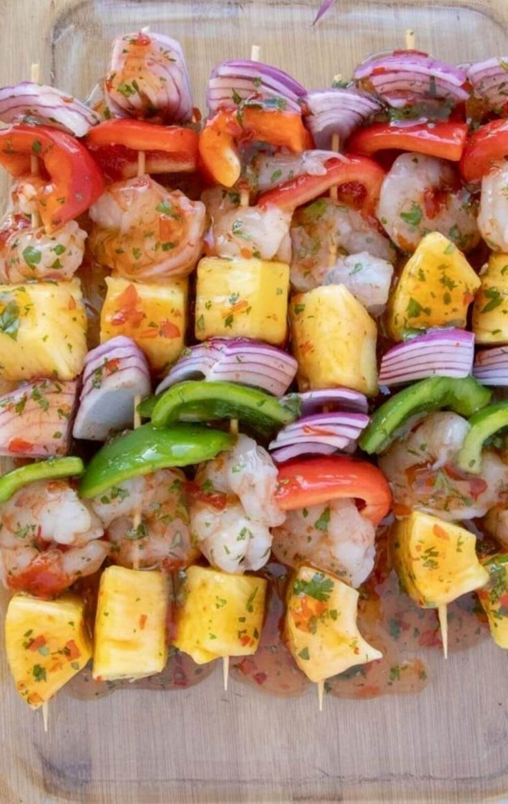 A pan of several colorful shrimp and pineapple skewers.