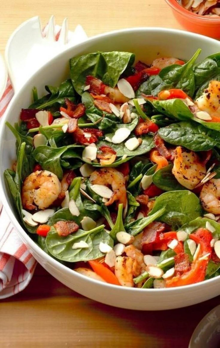 A healthy bowl of shrimp and spinach salad topped with hot bacon dressing.