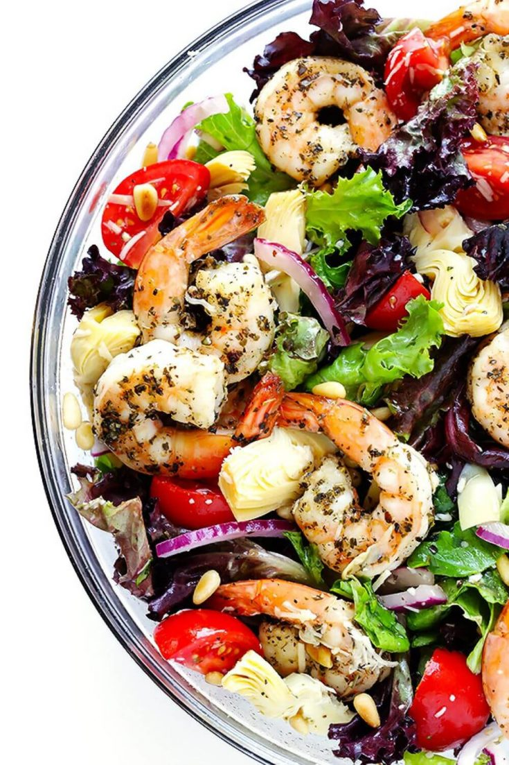 A closeup bowl of shrimp and artichoke green salad topped with lemon vinaigrette.