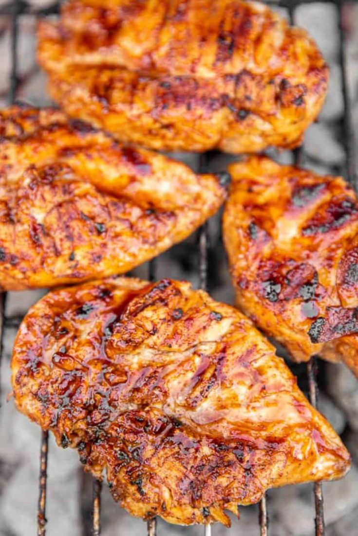 Several breasts of spicy pineapple brown sugar chicken on the grill.