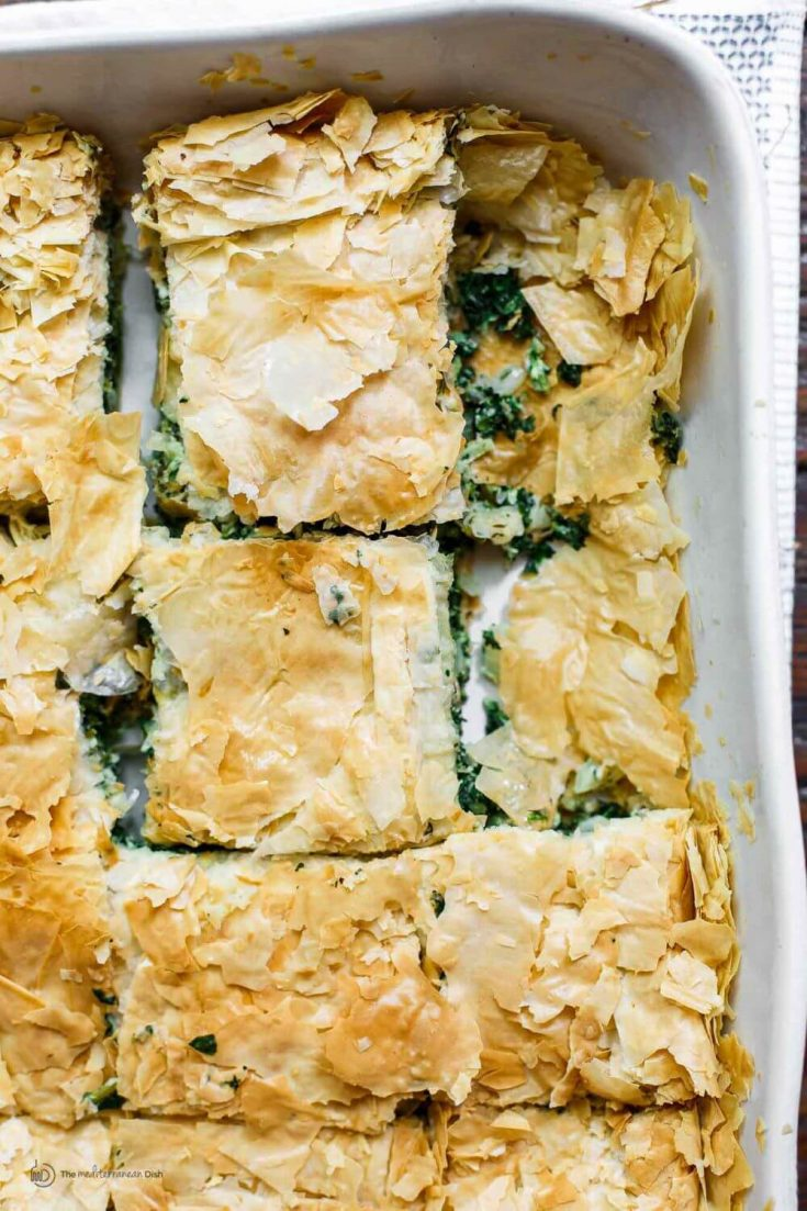 A large dish of spinach pie cut into pieces.