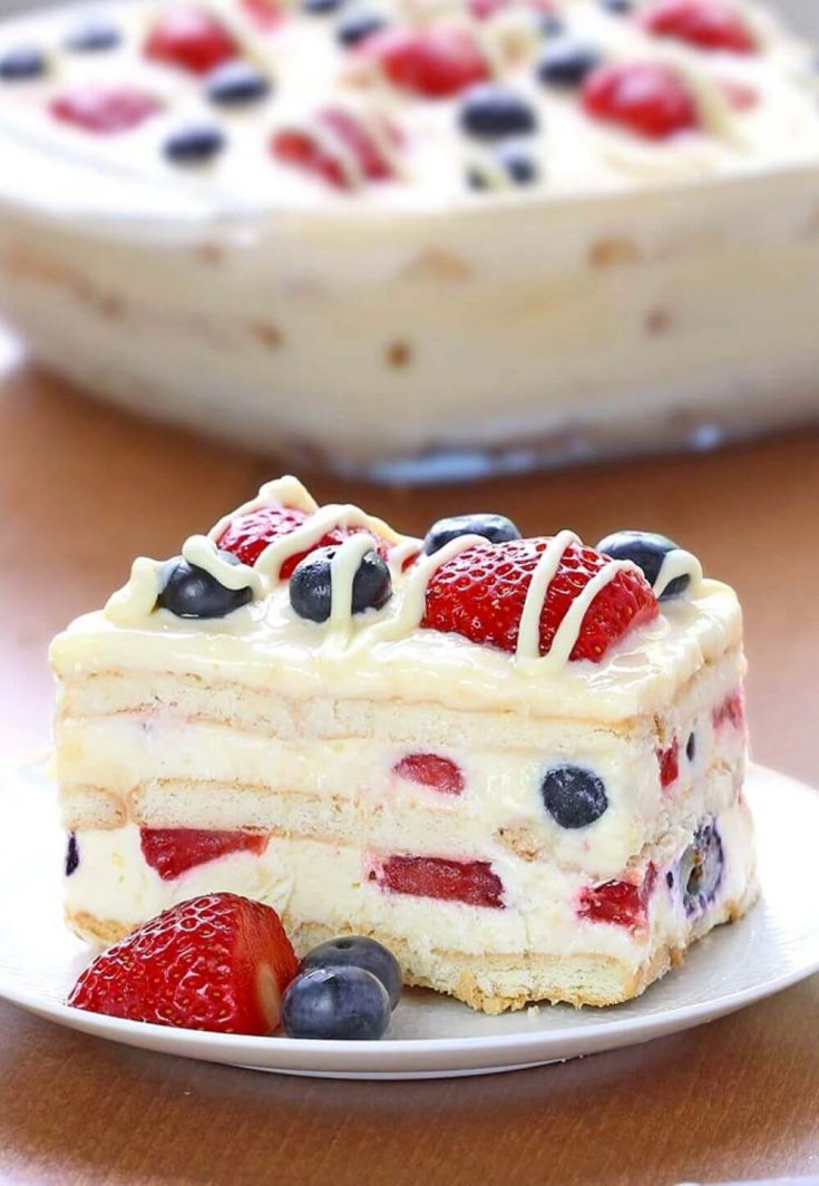 A colorful piece of no-bake summer berry icebox cake on a plate with berries.