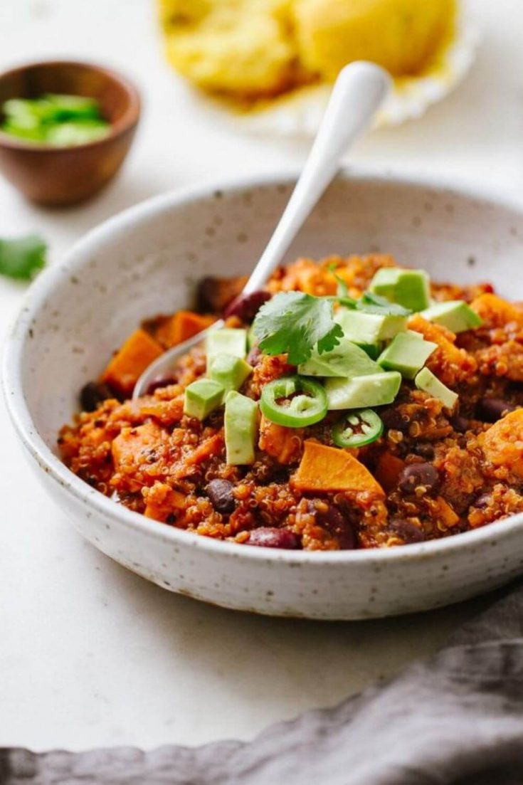 A delicious bowl of sweet potato and quinoa chili with a spoon.