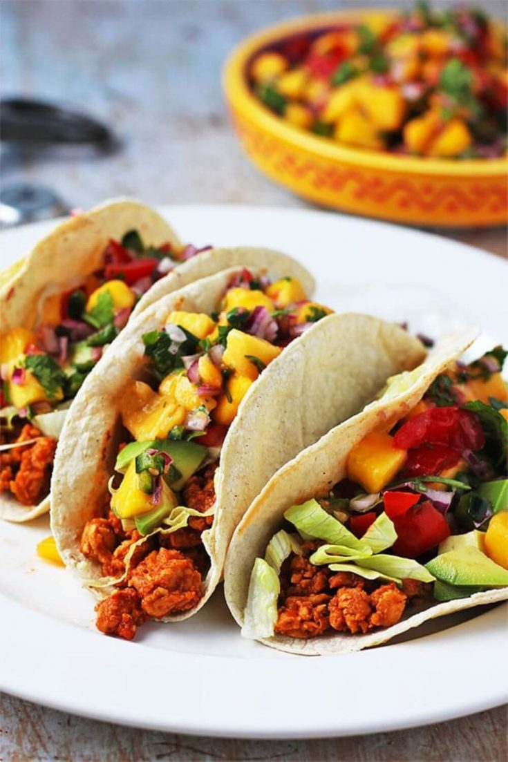A plate full of tempeh asada tacos topped with mango pico de gallo.