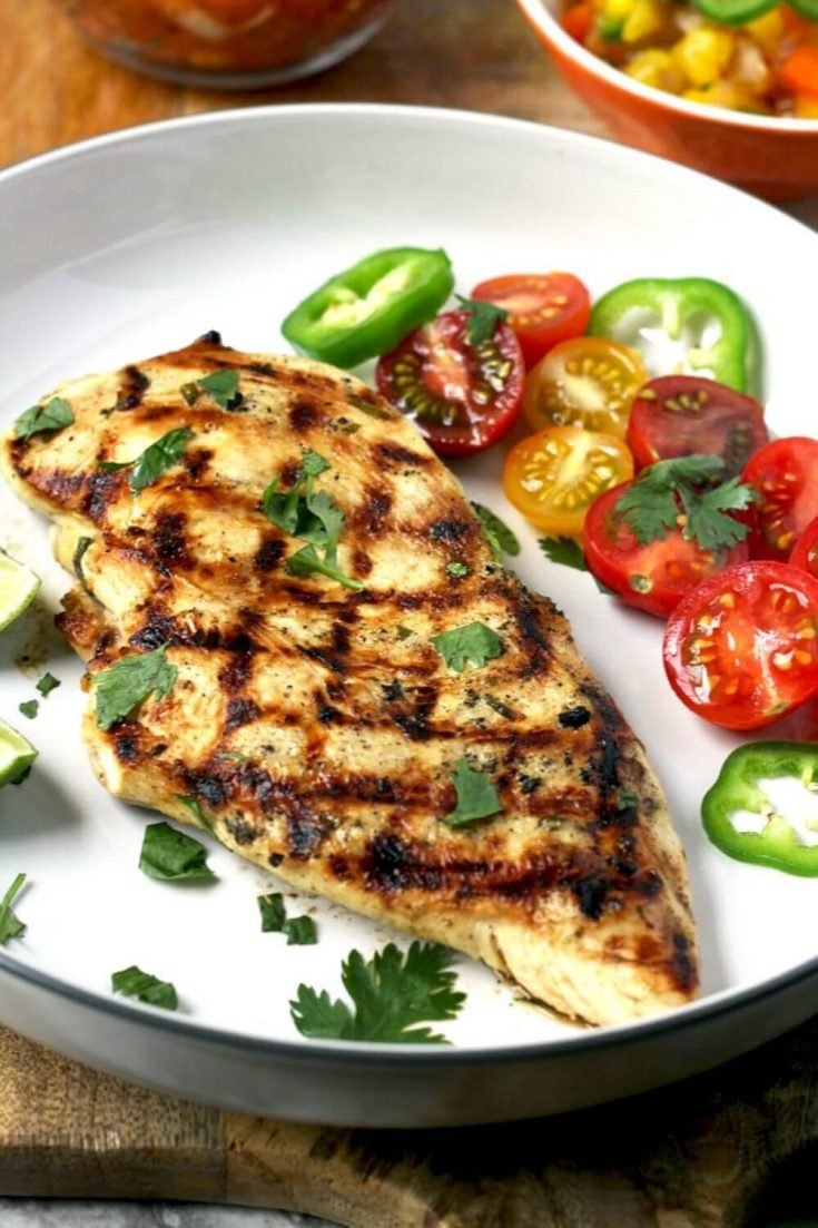 A plate of tequila lime grilled chicken with sliced tomatoes.