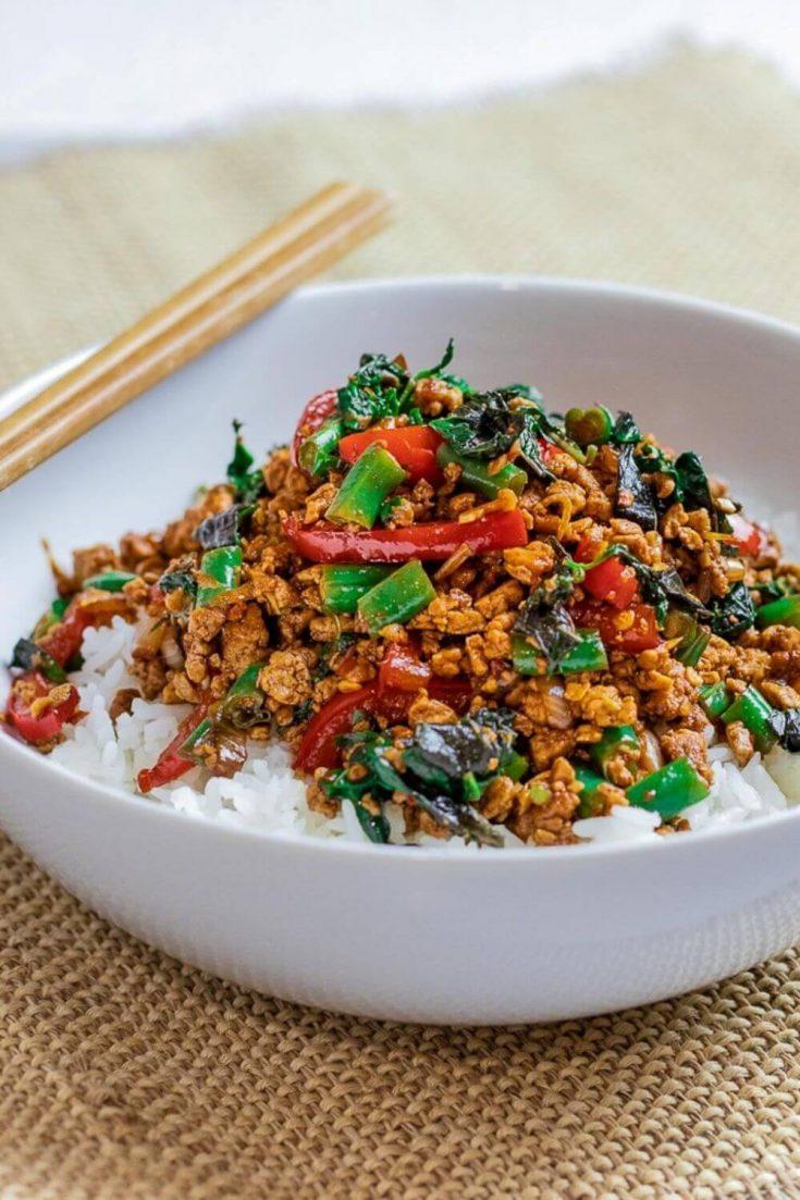 A bowl of Thai basil tofu stir fry over rice with chopsticks.