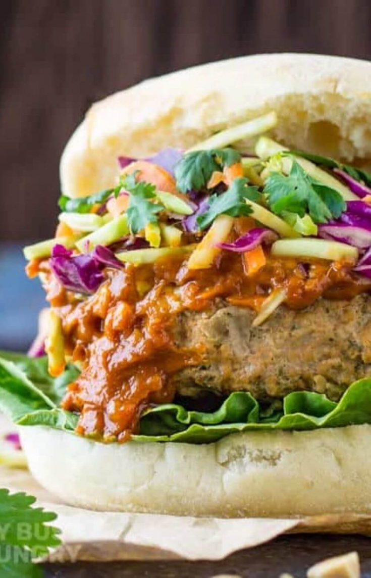 A close-up of a Thai turkey burger on a bun with slaw and sauce.