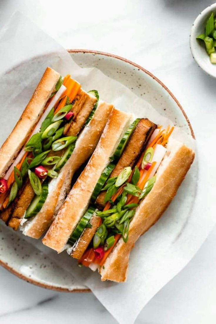 Two halves of a tofu banh mi sandwich on a plate.