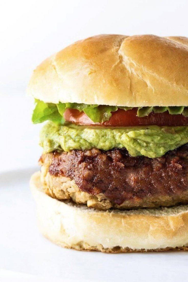 A closeup of a delicious veggie burger on a bun with guacamole, tomato, and lettuce.