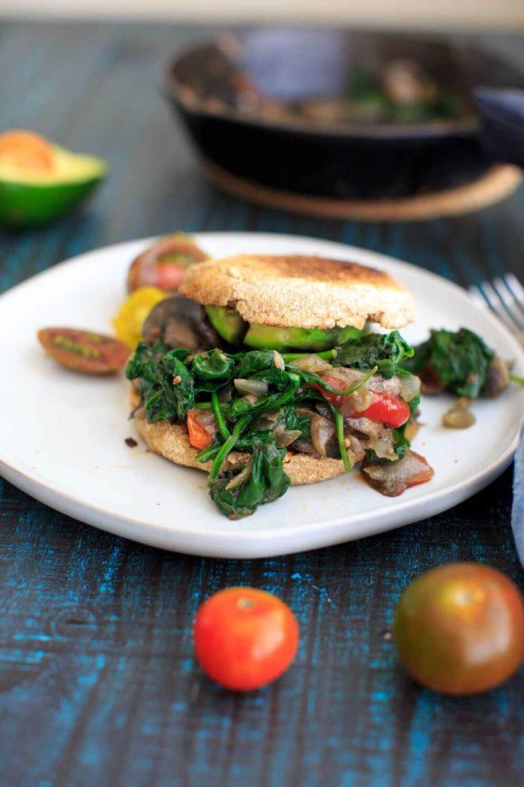 "A plate holding a small ""ultimate"" vegan breakfast sandwich."