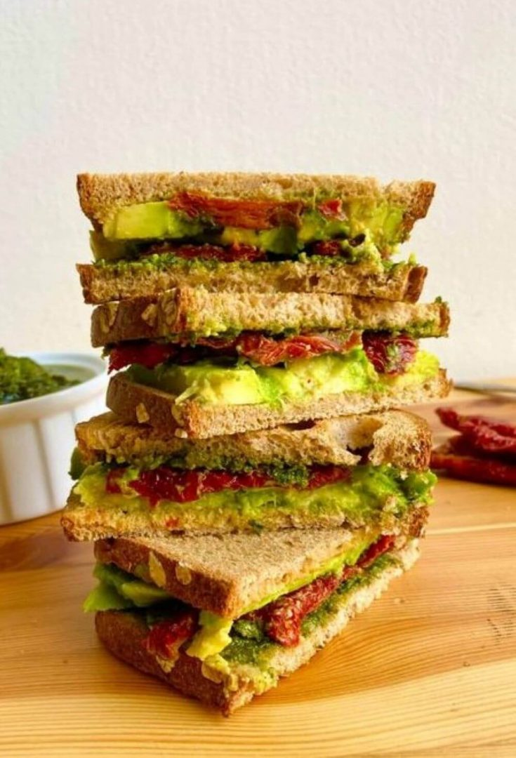A tall stack of vegan avocado sandwiches with pesto and sun-dried tomatoes.