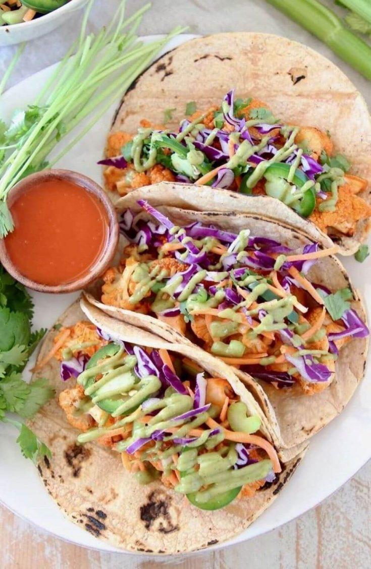 A plate of three vegan buffalo cauliflower tacos.