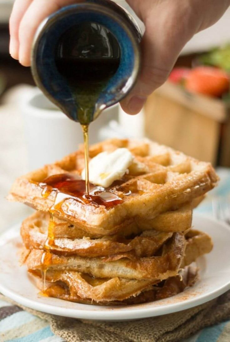 Maple syrup being poured on a stack of vegan french toast waffles.