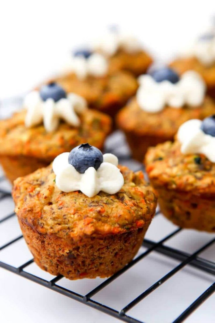 A healthy hidden veggie muffin with some frosting and a blueberry on top.