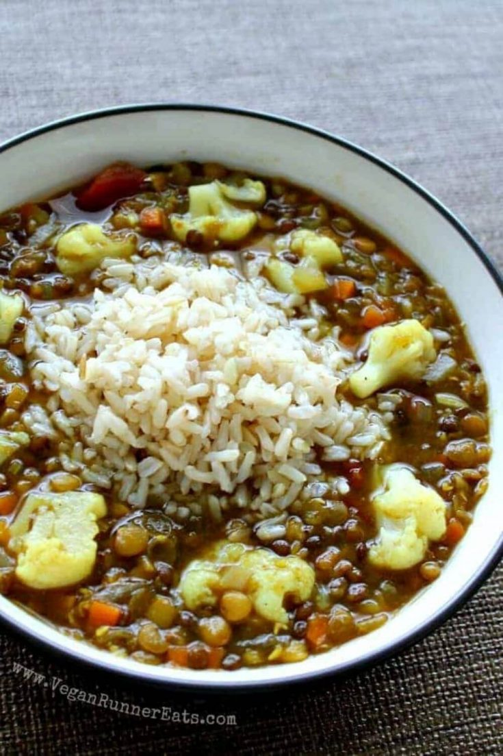 A large bowl of vegan lentil soup with cauliflower and rice.