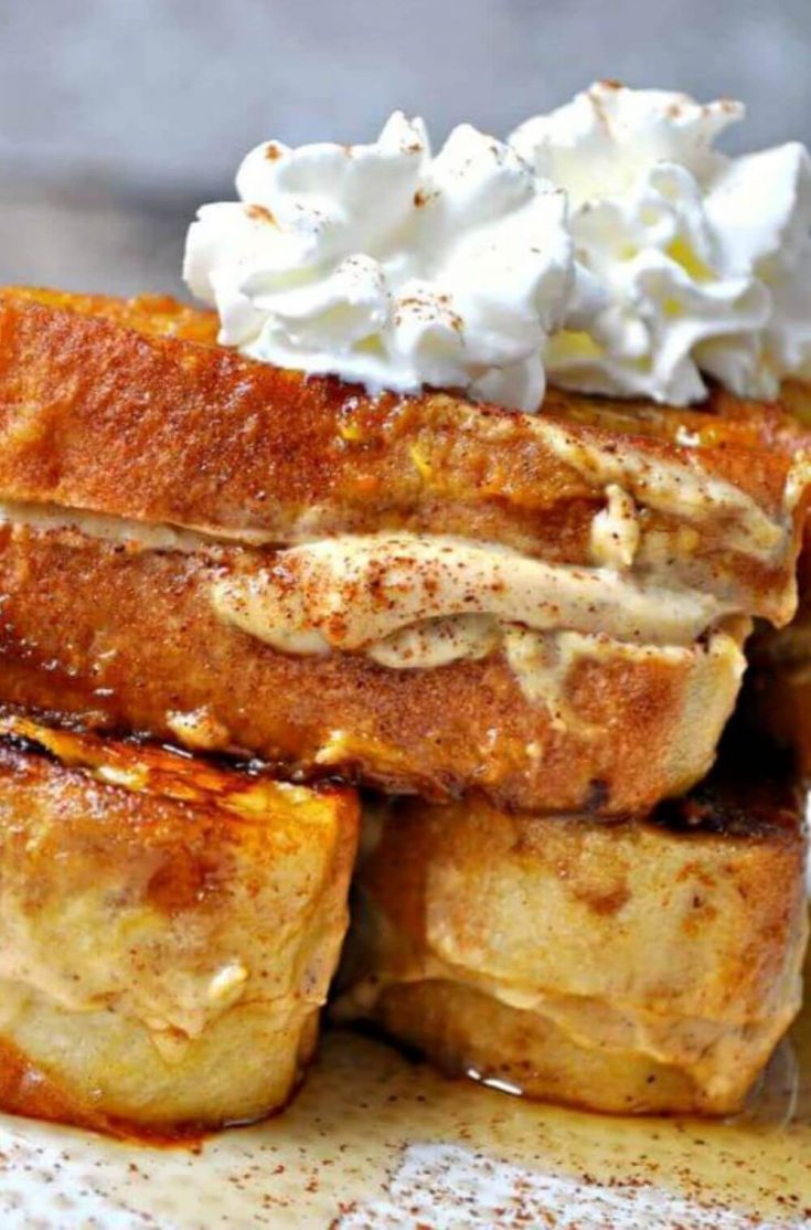 A close-up of a stack of vegan pumpkin cheesecake stuffed french toast topped with whipped cream.