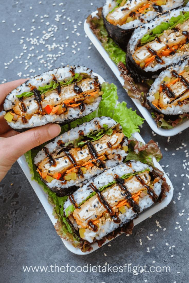 A tray of delicious vegan tofu katsu sushi sandwiches and rolls.
