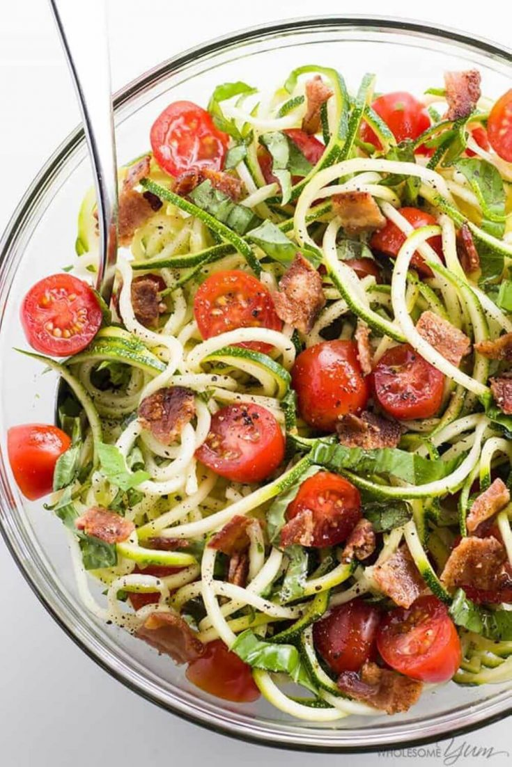A large bowl of zucchini noodle salad topped with bacon and tomatoes.