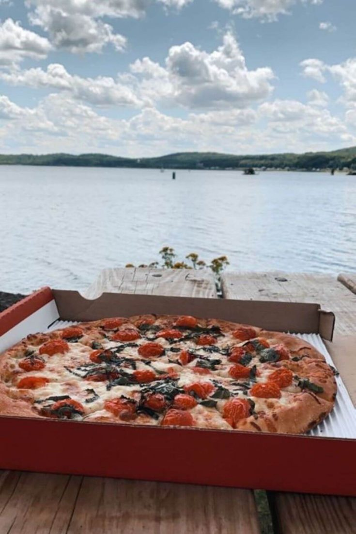 A large Margherita pizza from Aubree's with Lake Superior in the background.