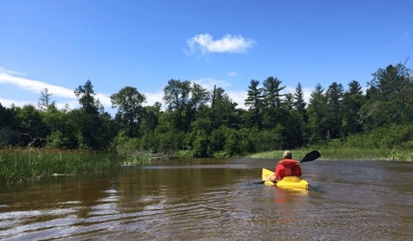 A man kayaking down the Au Train River with forest and grass on either side of the water.