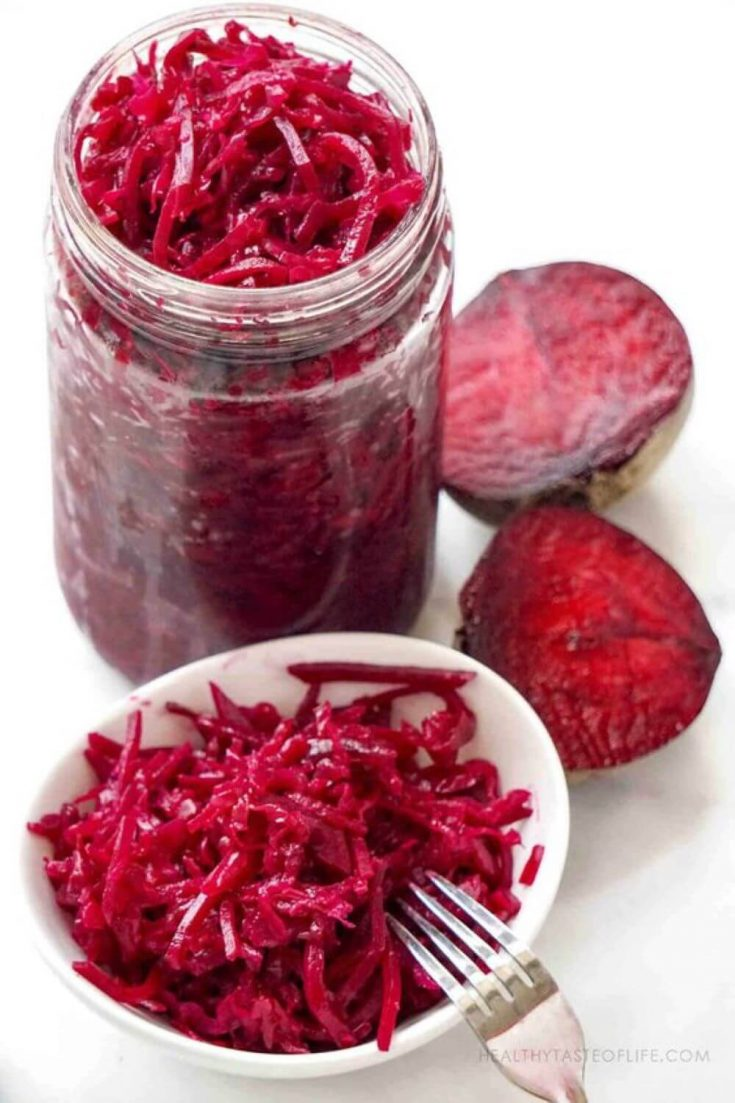 A jar and dish of beet and cabbage kraut.