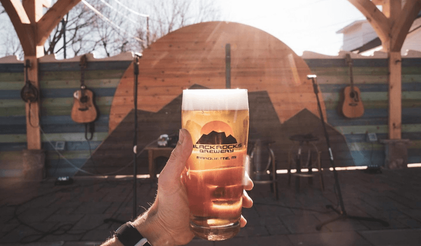 Someone holding a glass of beer in front of an outdoor music stage at Blackrocks Brewery.