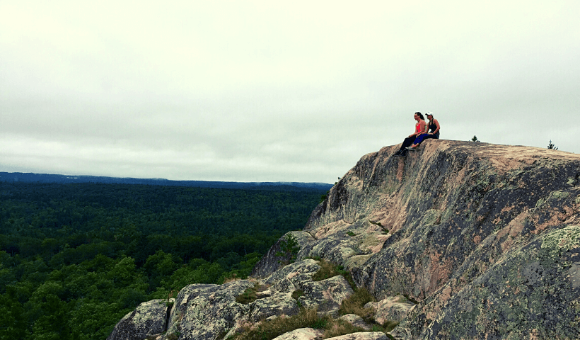 Two women sitting atop of a huge rock ledge on top of Hogback Mountain in Marquette, Mi.