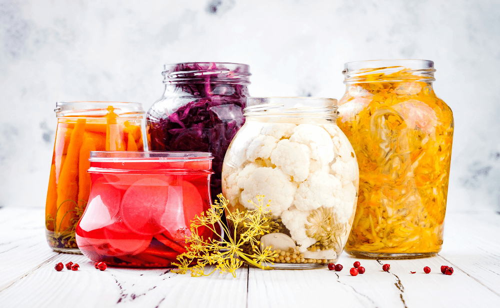 Five open jars of recently fermented vegetables.