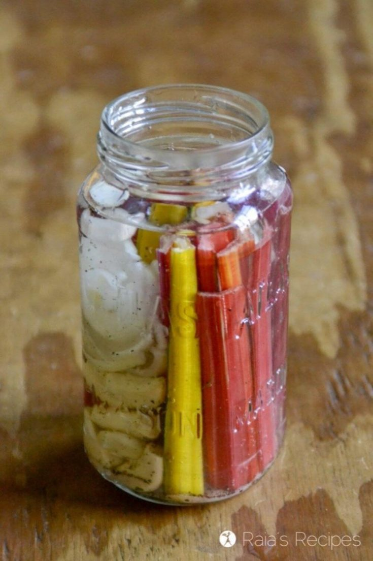 An open jar of colorful fermented rainbow chard.