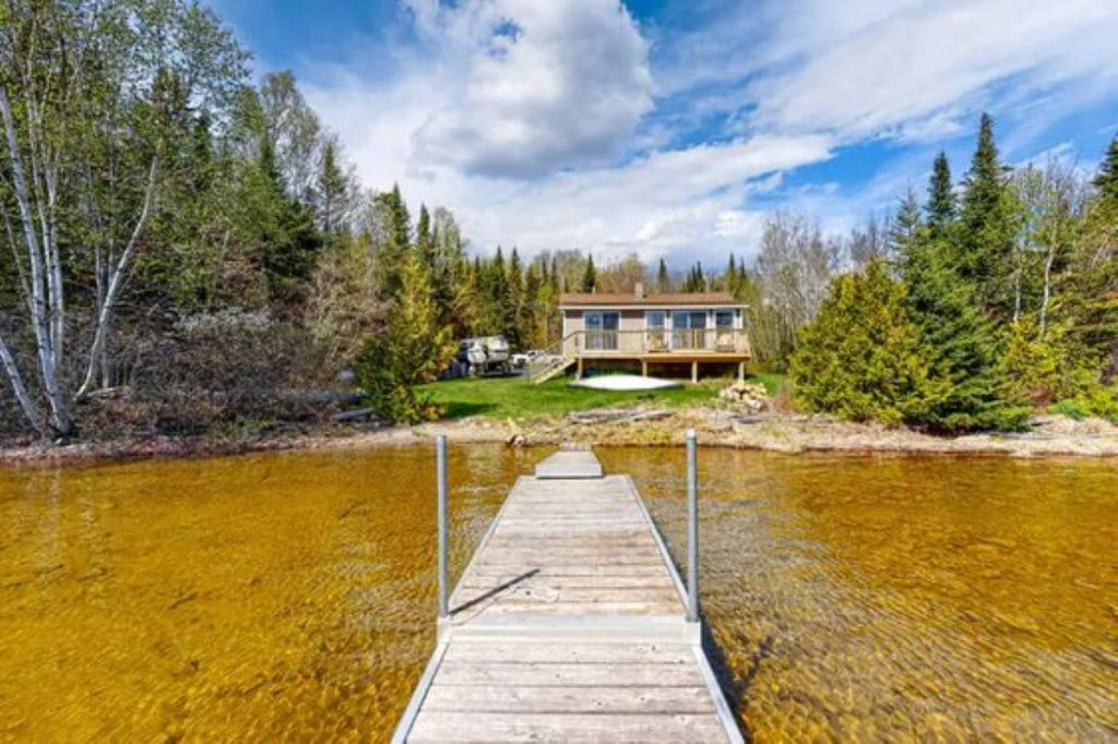 A lakefront cabin at the end of a long dock for rent in Maine.