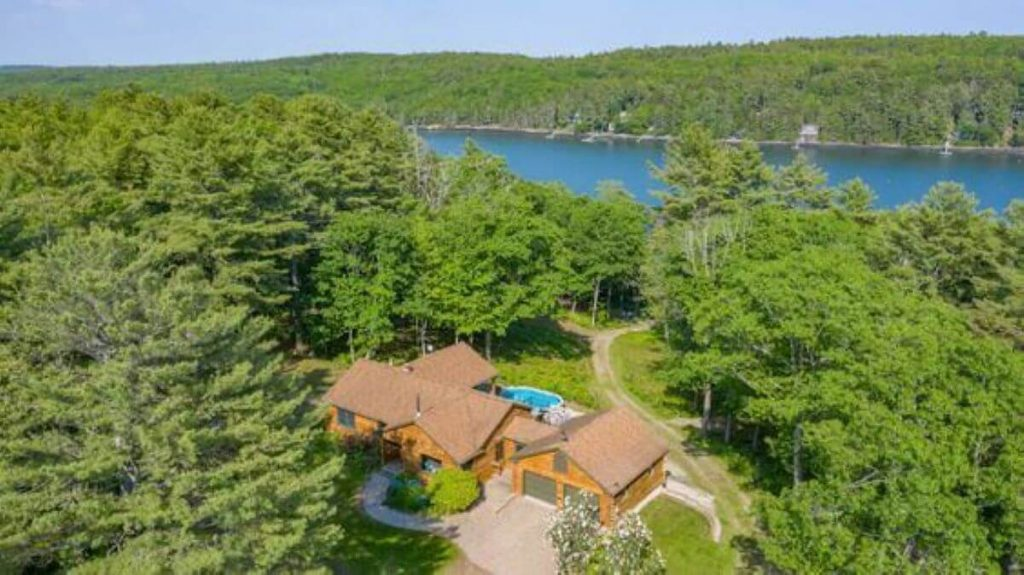 An overhead view of a large cabin rental in Maine surrounded by woods with a river in the background.