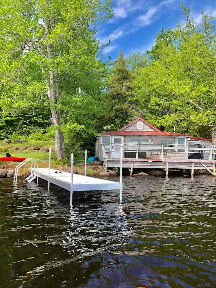 A small cabin on a lake in Maine next to a dock.
