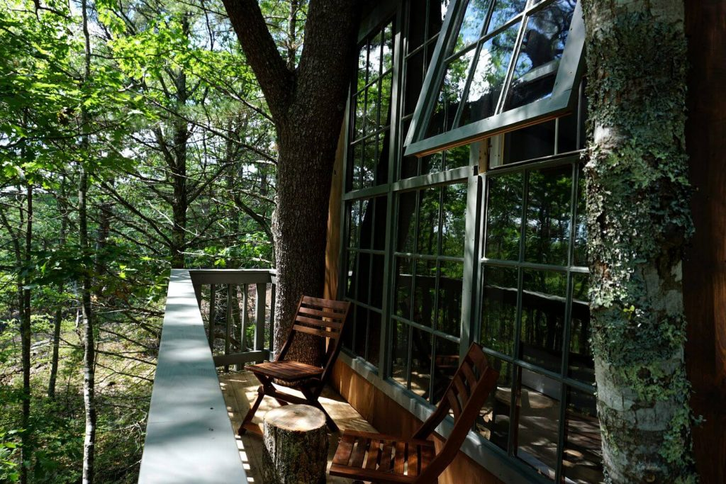 The outside decks and windows of a wooded cabin rental in Maine.