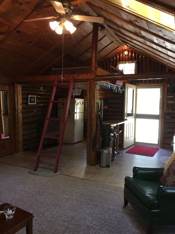 The inside of a cozy and romantic log cabin rental with a loft in Maine.