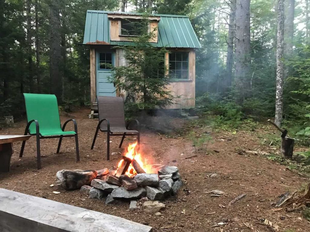 A small rustic cabin rental behind a campfire with seats around it.